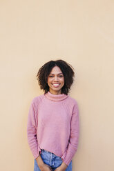 Portrait of smiling young woman wearing pink pullover leaning against wall - LOTF00038