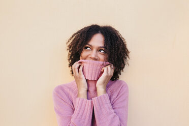 Young woman with afro hair covering her face with a pink turtleneck jumper. Studio shot. - LOTF00041