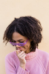 Portrait of smiling young woman wearing pink pullover and purple sunglasses - LOTF00044