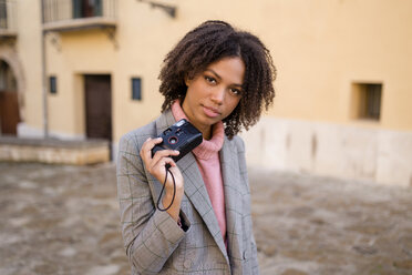 Mixed race woman holding a compact camera in the street. Palma, Mallorca, Balearic Islands, Spain. - LOTF00050