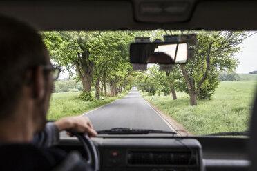 Germany, Ruegen, man driving car on an alley - MAMF00304