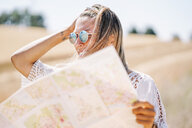 Blond young woman wearing mirrored sunglasses holding map looking at distance - OCMF00200