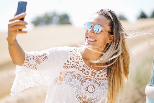 Portrait of blond young woman wearing mirrored sunglasses taking selfie with smartphone - OCMF00206