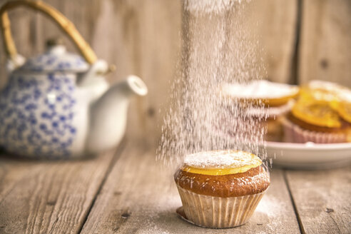 Sprinkling icing sugar on muffin with candied orange on top - EPF00529