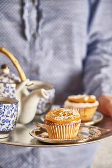 Woman serving fresh muffins and tea on silver platter, close-up - EPF00532