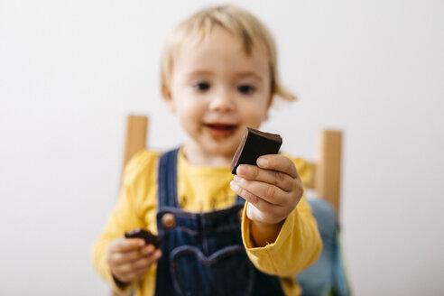 Hand of smiling toddler girl holding piece of chocolate, close-up - JRFF02329