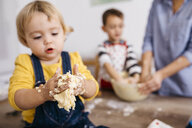 Toddler girl kneading dough with hers hands, close-up - JRFF02341