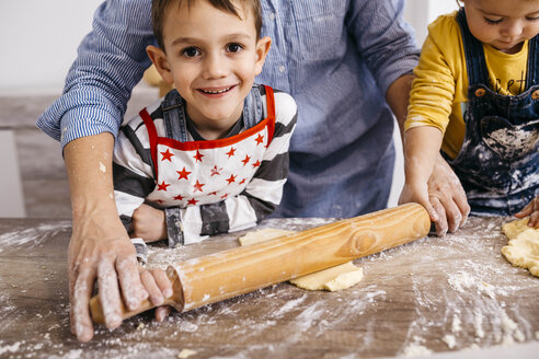 Portrait of happy boy baking cookies together with mother and little sister - JRFF02344