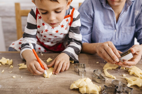Boy cutting out cookies with tool - JRFF02353