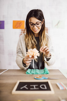 Young woman doing crafts at home, paper flowers - JRFF02360