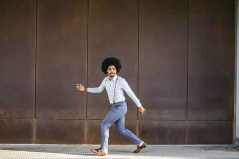 Portrait of man dancing in front of rusty metal wall - JRFF02399