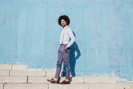 Portrait of stylish man standing in front of blue wall - JRFF02405