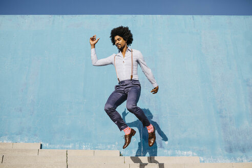 Stylish man jumping in the air in front of blue wall - JRFF02408
