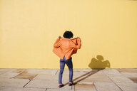 Back view of man wearing orange suit coat in front of yellow wall - JRFF02411