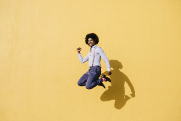 Smiling man jumping in the air in front of yellow wall - JRFF02414
