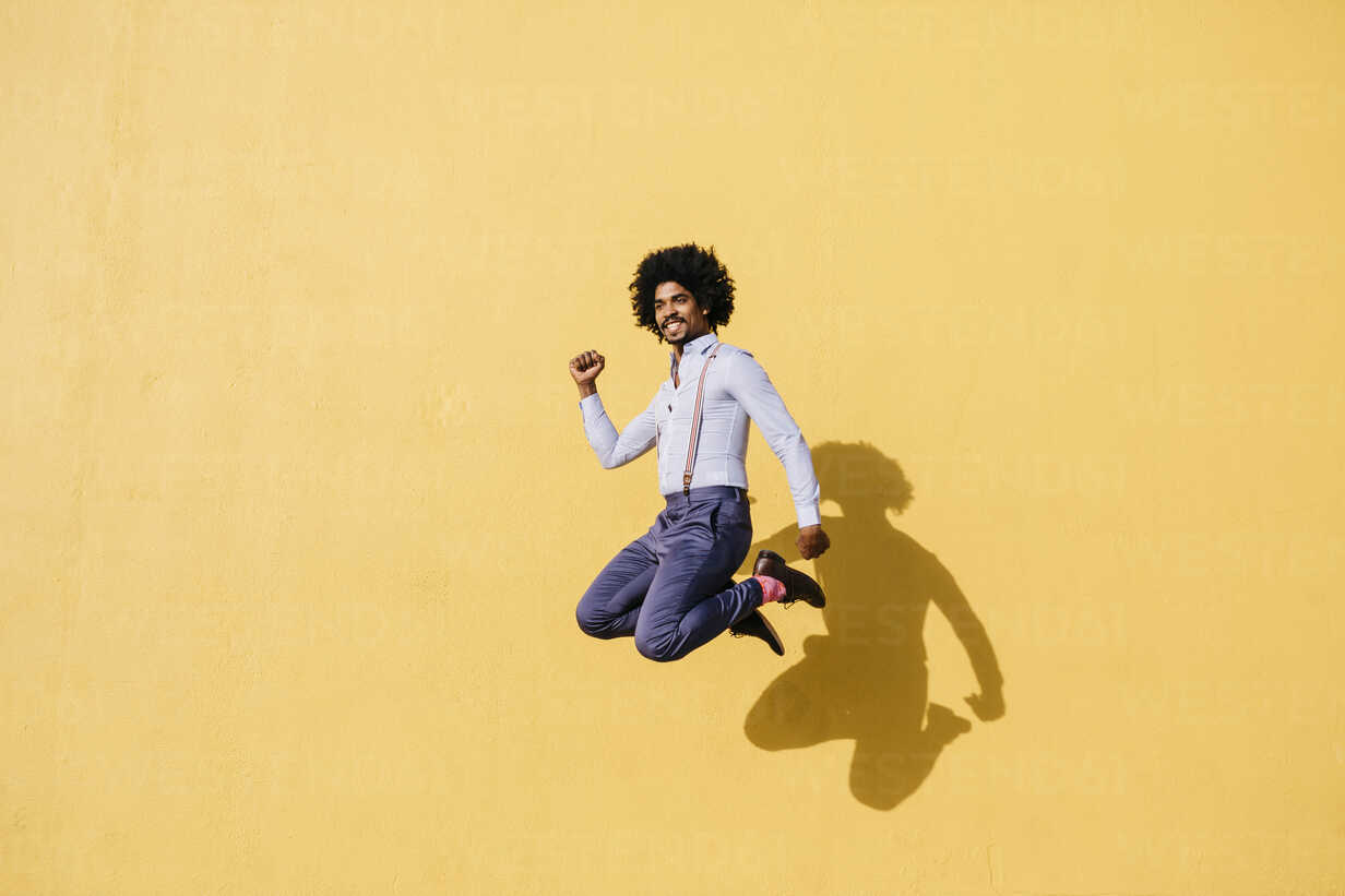 Smiling man jumping in the air in front of yellow wall - JRFF02414 - Josep Rovirosa/Westend61