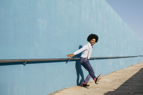 Man dancing in front of blue wall - JRFF02417