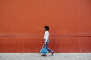 Man with bag walking down the street in front of a red wall - JRFF02438