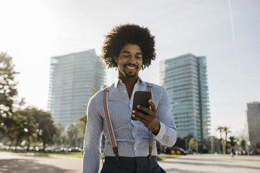 Spain, Barcelona, portrait of smiling man looking at cell phone - JRFF02441