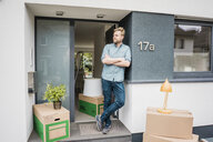 Man standing at house entrance surrounded by cardboard boxes - JOSF02684