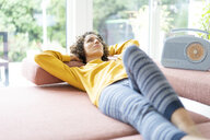 Woman lying on couch listening to music with portable radio at home - JOSF02699