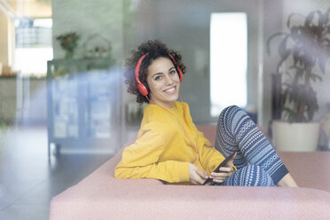 Happy woman listening to music on couch at home - JOSF02702
