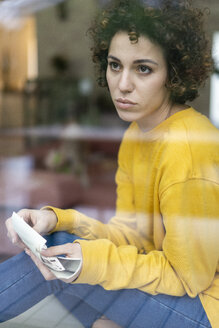 Serious woman sitting behind window at home holding photos - JOSF02720