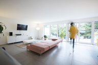 Woman moving in a spacious living room at home - JOSF02726