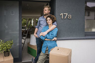 Couple standing at house entrance with cardboard boxes - JOSF02732