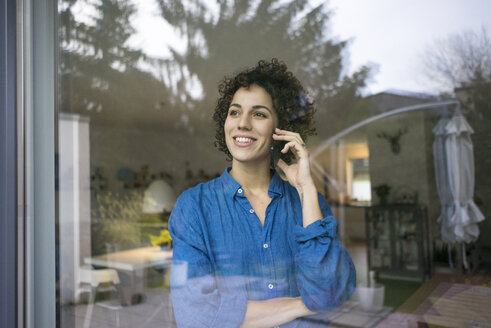Portrait of smiling woman on cell phone behind window at home - JOSF02735