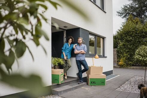 Couple standing at house entrance with cardboard boxes - JOSF02741