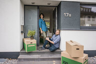 Couple at house entrance with cardboard boxes - JOSF02744