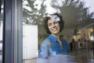 Portrait of smiling woman at home looking out ofwindow - JOSF02747