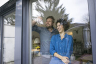 Happy couple behind window at home looking out - JOSF02750