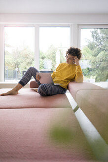 Woman using laptop on couch at home - JOSF02753