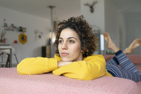 Woman lying on couch at home thinking - JOSF02756
