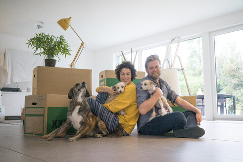 Happy couple sitting in living room with dogs and cardboard boxes - JOSF02759