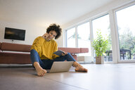 Smiling woman using laptop and tablet at home - JOSF02768