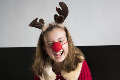 Laughing girl wearing a reindeer mask at home - XCF00194