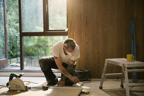 Construction worker measuring wood board in house - HOXF04234