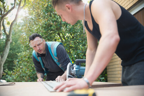 Construction workers measuring wood in driveway - HOXF04255