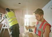 Construction workers plastering in house - HOXF04264