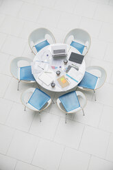 High angle view business laptop and paperwork on round table - HOXF04312