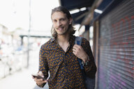 Portrait confident hipster man with smart phone on urban sidewalk - CAIF22433