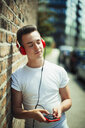 Serene young woman listening to music with headphones and mp3 player - CAIF22457