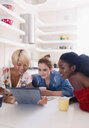 Young women friends using digital tablet at kitchen table - CAIF22463