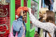 Young women helping friend adjusting headscarf on urban sidewalk - CAIF22466