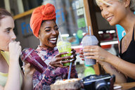 Young women friends drinking smoothies at sidewalk cafe - CAIF22472