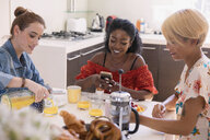 Young women friends enjoying breakfast at kitchen table - CAIF22478