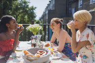 Young women friends enjoying brunch on sunny apartment balcony - CAIF22484